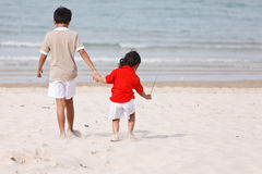 Asian boys holding hands on beach Royalty Free Stock Images