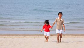 Asian boys holding hands on beach Stock Image