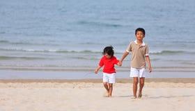 Asian Boys Holding Hands On Beach Stock Image