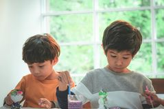 Boys painting a doll in Art classroom, for creativity conc. Asian boys painting a doll in Art classroom, for creativity concept royalty free stock photo