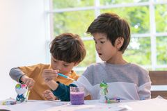 Boys painting a doll in Art classroom, for creativity conc. Asian boys painting a doll in Art classroom, for creativity concept stock photo