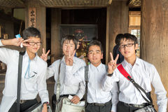 Asian boys peace and victory sign. Four young Japanese boys giving the peace or victory sign with their hands, Kyoto, Japan Royalty Free Stock Photos
