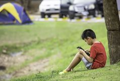 Asian Boys play telephone on the lawn Background blurry image of the car and tent.  stock photography