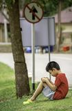 Asian Boys play telephone on the lawn Background blurry image of road.  stock photos
