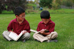 Asian boys reading. Little asian boys sitting in grass with books stock photo