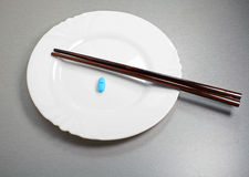 Asian breakfast. Blue pill and chopsticks on a white plate Stock Images
