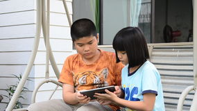 Asian brethren using tablet. Asian brethren using tablet together on the swings in the park stock footage