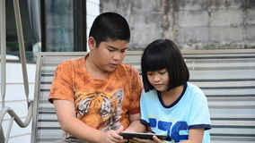 Asian brethren using tablet. Asian brethren using tablet together on the swings in the park stock video footage