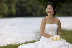 Asian Bride 10. A beautiful young asian woman in a wedding dress poses by a lake Stock Photography