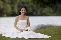 Asian Bride 11. A beautiful asian bride sits by a lake in her wedding dress Stock Images