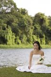 Asian Bride 12. A beautiful asian woman sits by a lake in her wedding dress Royalty Free Stock Photo