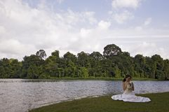 Asian Bride 13. A beautiful asian woman sits by the side of a lake in Singapore in her wedding dress Royalty Free Stock Image