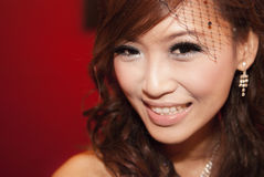 Asian bride. Beautiful Asian bride smiling, against red background Stock Images