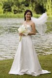 Asian Bride 17. An asian woman stands near a lake in her wedding dress, the veil flying in the wind stock image