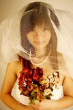 Asian bride. With her veil and flowers royalty free stock image