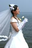 Asian bride. Young beautiful bride holding flower on beach Stock Photos