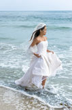 Asian bride at beach. A beautiful Asian bride wearing her wedding dress wades through the surf at the beach just after her wedding Stock Images