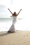 Asian Bride Celebrating Her Joy on the Beach. Happy Asian Bride Celebrating Her Joy on the Beach in the Ocean Stock Photo