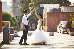 Asian bride and groom dancing in parking lot Royalty Free Stock Photo
