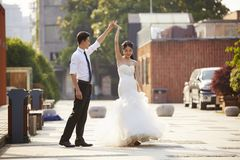 Asian bride and groom dancing in parking lot Stock Photos