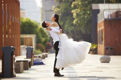 Asian bride and groom hugging outdoors. Asian newly wed bride and groom celebrating marriage and hugging outside a building Royalty Free Stock Image