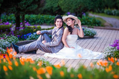 Asian Bride and Groom Sitting Together in Garden.  Stock Photo