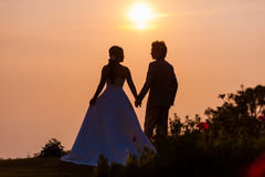 Asian Bride and Groom Standing on Mountain at Sunset Royalty Free Stock Image