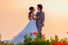 Asian Bride and Groom Standing on Mountain at Sunset Stock Photo