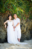 Asian bride and groom on a tropical beach. Wedding and honeymoo Royalty Free Stock Image