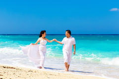 Asian bride and groom on a tropical beach. Wedding and honeymoo Stock Photo