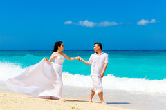 Asian bride and groom on a tropical beach. Wedding and honeymoon. Concept Royalty Free Stock Images