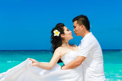 Asian bride and groom on a tropical beach. Wedding and honeymoon Royalty Free Stock Photos