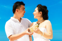 Asian bride and groom on a tropical beach. Wedding and honeymoon. Concept Royalty Free Stock Photography