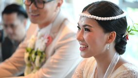 Asian bride on hands pouring blessing water into groom and bride`s bands.  stock video footage