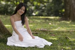 Asian Bride Outdoors 2. A beautiful young woman in her wedding dress sits under a big tropical tree Royalty Free Stock Images