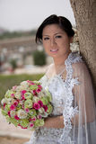 Asian bride outside holding a bouquet Stock Photos