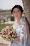 Asian bride outside holding a bouquet Stock Photos