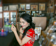 Asian bride in red cheongsam dress putting on her lipstick stock image