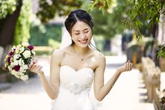 Asian bride rejoicing with bouquet in hand Royalty Free Stock Image