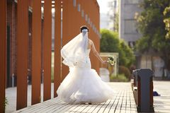 Rear view of an asian bride. Asian bride in white wedding dress walking with a bouquet, rear view Stock Photo