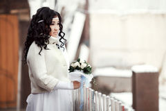 Asian bride in a winter coat standing outdoors looks into the distance. Copy space. Royalty Free Stock Images