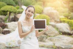 Asian bride woman holding and show digital tablet feeling so happiness. The asian bride woman holding and show digital tablet feeling so happiness Stock Photo