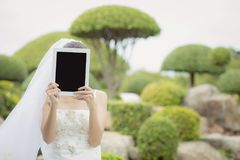 Asian bride woman holding and show digital tablet feeling so happiness. The asian bride woman holding and show digital tablet feeling so happiness Stock Photos