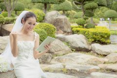 Asian bride woman holding and show digital tablet feeling so happiness and glad. The asian bride woman holding and show digital tablet feeling so happiness and Stock Image
