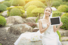 Asian bride woman holding and show digital tablet feeling so happy. Asian bride woman holding and show digital tablet feeling so happiness Royalty Free Stock Photography