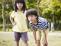 Asian brother and sister. Little asian boy and girl playing outdoors Stock Image
