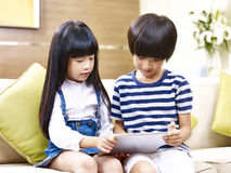 Asian brother and sister using digital tablet at home Royalty Free Stock Images