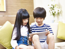 Asian brother and sister using digital tablet. Little asian brother and sister sitting on couch using digital tablet together Royalty Free Stock Photography