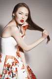 Asian brunette in gorgeous dress touching hair. Stock Photo