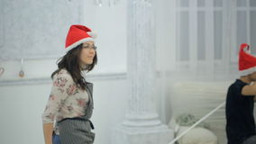 Asian brunette with hammer in red Santa Claus hat makes repairs stock video footage